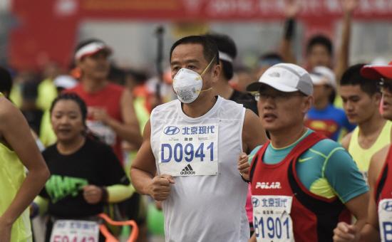 Un alergător poartă o masca de protecţie în timp ce participaă la cel de-al 35-lea Maraton Internaţional din Beijing în 20 septembrie 2015.