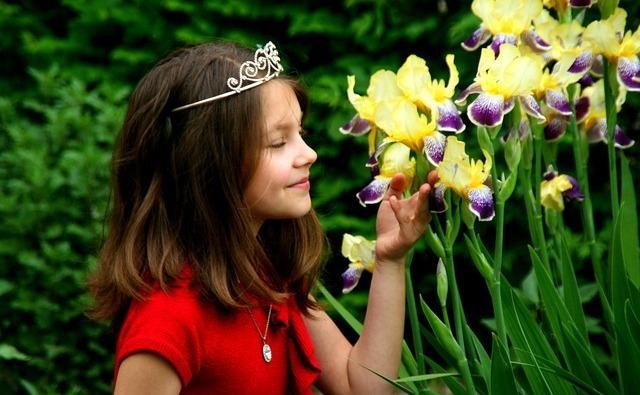 O fetiţă miroase florile