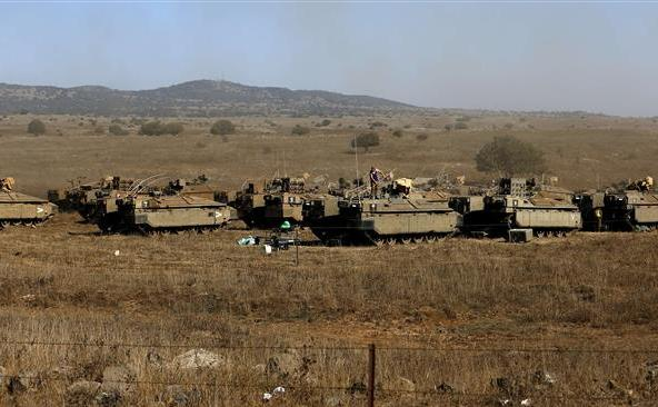 Soldaţi israelieni stau pe transportoarele lor blindate în partea israeliană a Înălţimilor golan, 21 august 2015.