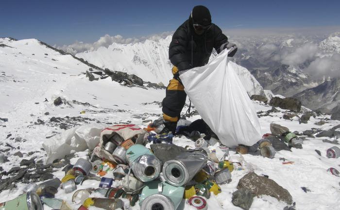 Un Sherpa nepalez adunând gunoaie la 8000 de metri într-o expediţie de salubrizare a Everest-ului - strângând echipament şi resturi lăsate în urmă de alpinişti - dar şi cadavre, mai 2010