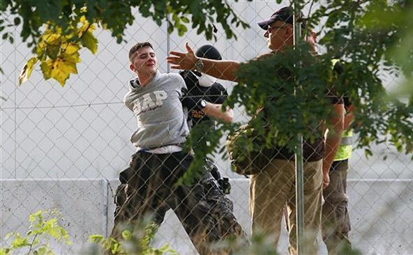 Poliţia ungară arestează un tânăr refugiat la graniţa sârbo-ungară, 16 septembrie 2015.