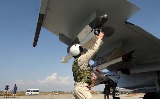 Un pilot rus fixează o rachetă aer-aer pe avionul său Su-30 înainte să decoleze de la baza aeriană Hmeimim din Siria, 5 octombrie 2015.