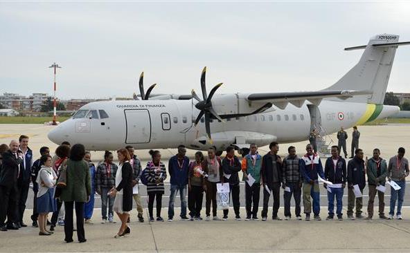 Un grup de refugiaţi eritreeni se îmbarcă într-un avion pe aeroportul Ciampino din Italia pentru a călători în Suedia.