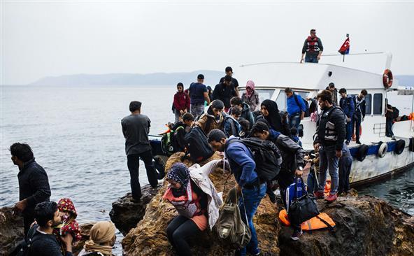 Un grup de refugiaţi soseşte pe insula elenă Lesbos după ce au traversat Marea Egee din Turcia, 11 octombrie 2015.