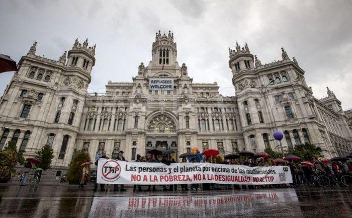 Manifestanţii afişează un banner mare în faţa Primăriei din Madrid în timpul unui protest anti-TTIP în capitala Spaniei, 17 octombrie 2015.