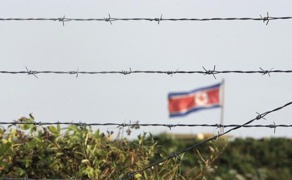 Un steag nord-coreean este văzut după un gard de sârmă ghimpată.