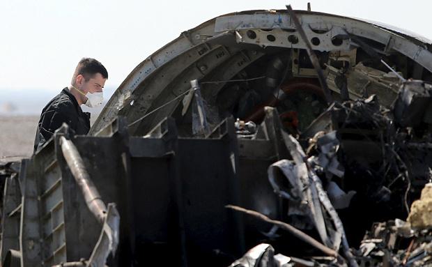 Un investigator militar din Rusia stă lângă rămăşiţele avionului rusesc Airbus A321 prăbuşit în peninsula egipteană Sinai.