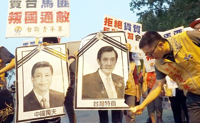 Un susţinător al independenţei Taiwanului încearcă să aprindă portretele liderului chinez Xi Jinping (st) şi al omologului său taiwanez Ma Ying-jeou la aeroportul din Taipei, 7 noiembrie 2015.