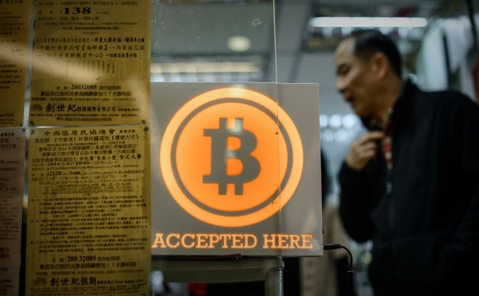 Logo-ul Bitcoin afişat pe geamul primului punct de schimb din Hong Kong
