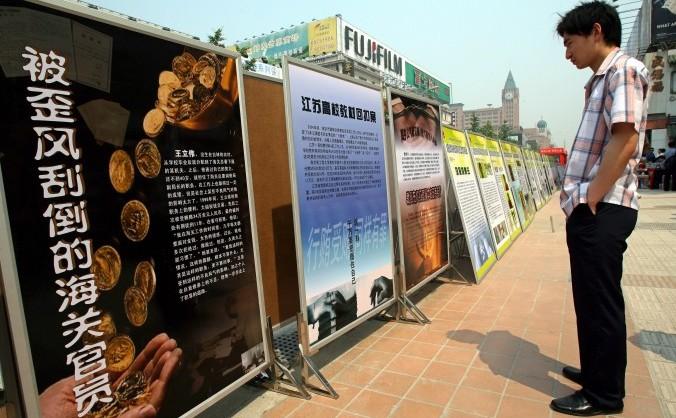 Un chinez se uită la o serie de panouri propagandistice ce conţin mesaje împotriva anticorupţiei, afişate în Beijing, 11 iunie 2007.