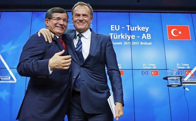 Premierul turc Ahmet Davutoglu (st) şi preşedintele Consiliului European Donald Tusk se felicită după finalizarea summitului UE-Turcia din Bruxelles, 29 noiembrie 2015.
