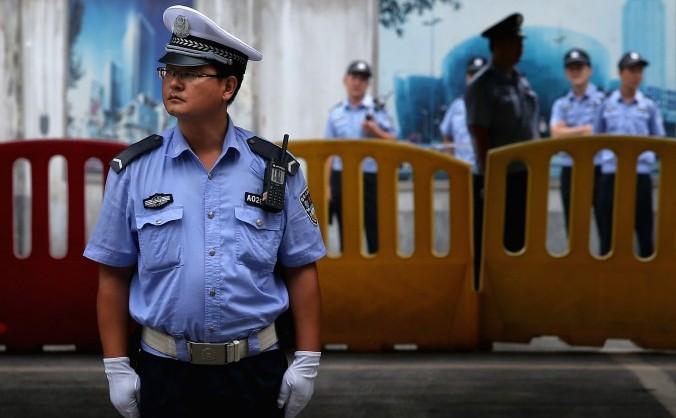 Mai mulţi poliţişti stau în faţa Tribunalului Intermediar al Poporului din Jinan, 25 august 2013, China.