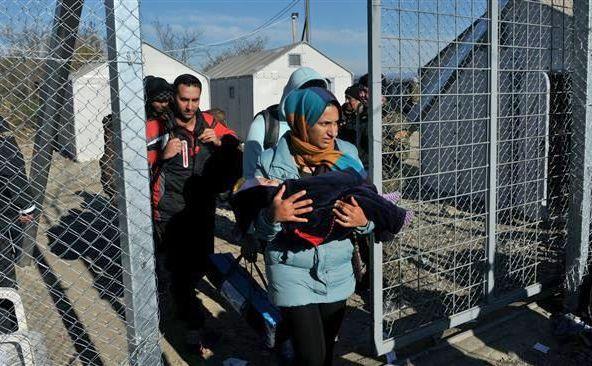 Refugiaţi care nu au primit permisiunea să treacă graniţa dintre Grecia şi Macedonia sunt escortaţi de poliţie înapoi în partea elenă a graniţei, 8 decembrie 2015.