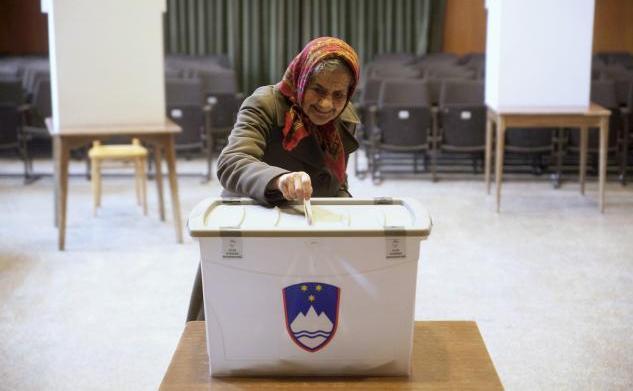 O femeie îşi depune buletinul de vot la o secţie de votare din Sora, Slovenia, în timpul unui referendum privind acordarea dreptului de a se căsători şi de a adopta copii în cazul cuplurilor de homosexuali, 20 decembrie 2015.