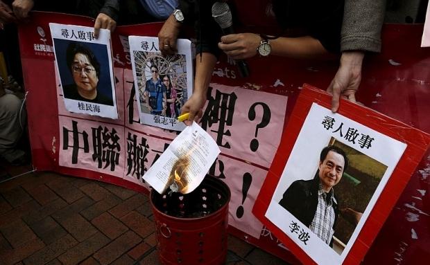 Un manifestant pro-democraţie arde o scrisoare lângă pozele lui (de la stânga la dreapta) Gui Minhai, Cheung Jiping şi Lee Bo, în timpul unui protest în care s-a cerut lansarea unei investigaţii asupra dispariţiei lor în Hong Kong, 3 ianuarie 2016.