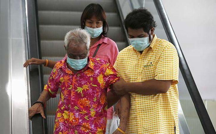 Oamenii poartă măşti de protecţie pentru a preveni contractarea virusului MERS în Tailanda, 19 iunie 2015. Virusul a reapărut în 2016 în ţara asiatică.