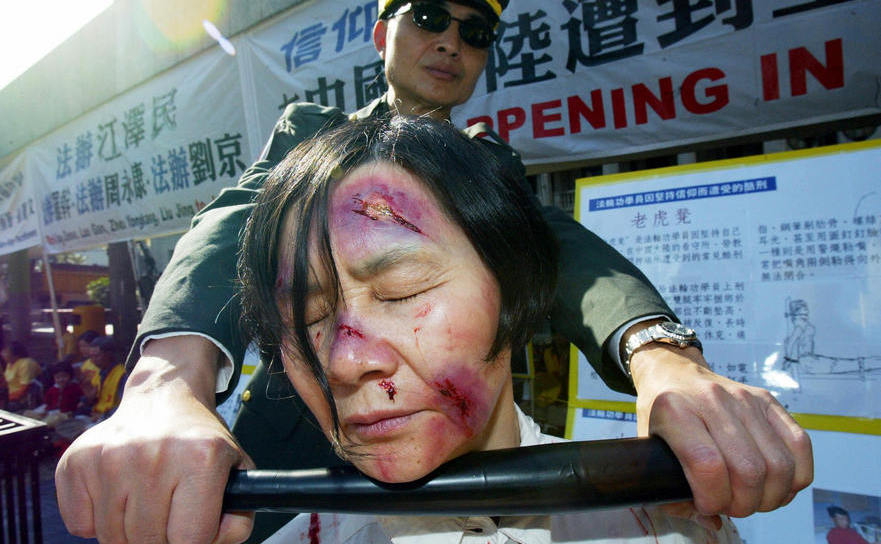 PUNERE ÎN SCENĂ a torturilor la care sunt supuşi aderenţii Falun Gong în China de către Partidul Comunist. Hong Kong, 2004