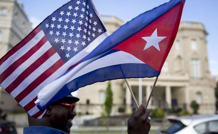 Un bărbat ţine în mâna sa două steguleţe, unul american şi altul cubanez.