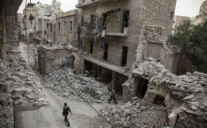 Un bărbat sirian trece pe lângă clădiri distrus în cartierul Bab al-Hadid din oraşul Alep, 2 mai 2016.