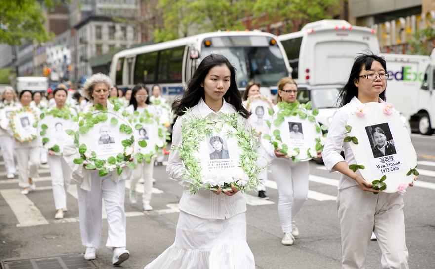Aderenţi Falun Gong purtând poze ale celor ucişi de regimul comunist, 13 mai 2016.