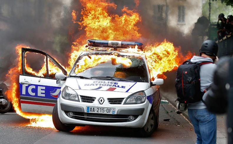 O maşină de poliţie incendiată în timpul unei demonstraţii împotriva violenţei poliţieneşti şi împotrivita modificării codului muncii în Paris, Franţa, 18 mai 2016.