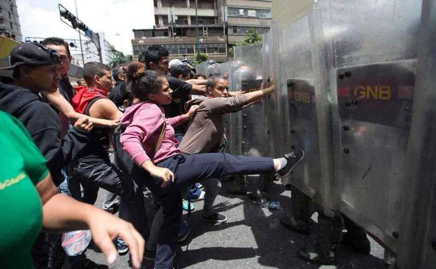 O femeie loveşte scutul unui soldat al Gărzii Naţionale în timpul unei demonstraţii anti-guvern în capitala venezueleană Caracas, 2 iunie 2016.