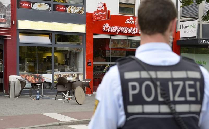Un ofiţer de poliţie stă în faţa unui restaurant din oraşul german Reutlingen, 24 iulie 2016, unde un refugiat sirian a ucis o femeie şi a rănit alte două persoane cu o macetă.