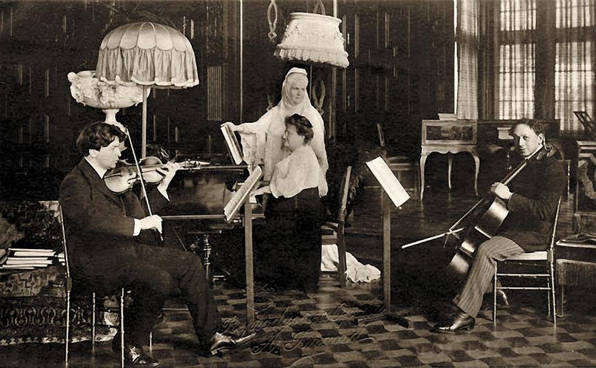 """George Enescu la unul dintre concertele Reginei Carmen Sylva (Regina Elisabeta a României), pe care marele compozitor o evoca drept """"o  prezenţă supraomenească, o fiinţă cu nimb, departată de oamenii obişnuiţi,  revărsând numai lumină şi bunătate""""."""