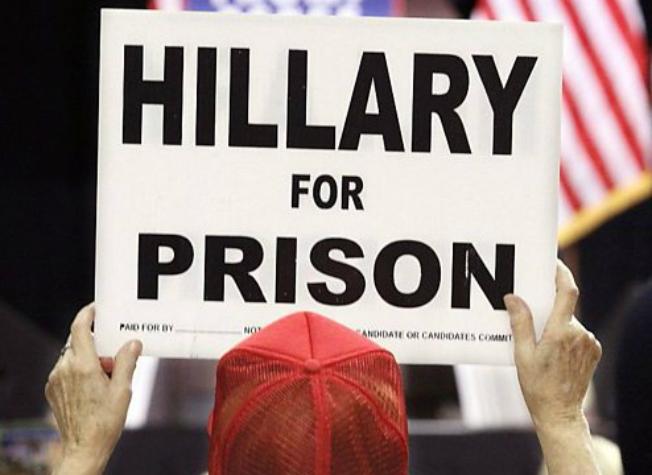Un suporter a lui Donald Trump tine o pancartă care cere arestarea lui Hillary Clinton