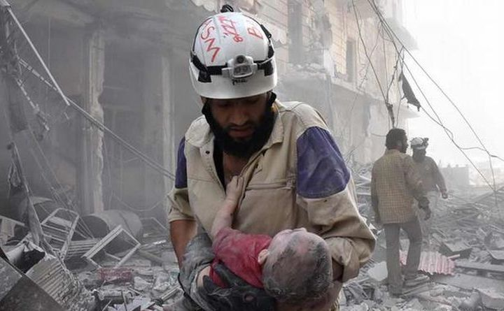 Un membru al Căştilor Albe Siriene salvează un copil dintre ruinele provocate de bombardamentele asupra oraşului sirian Alep.
