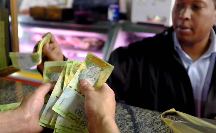 Un casier numără bani într-o piaţă publică din Caracas, Venezuela.