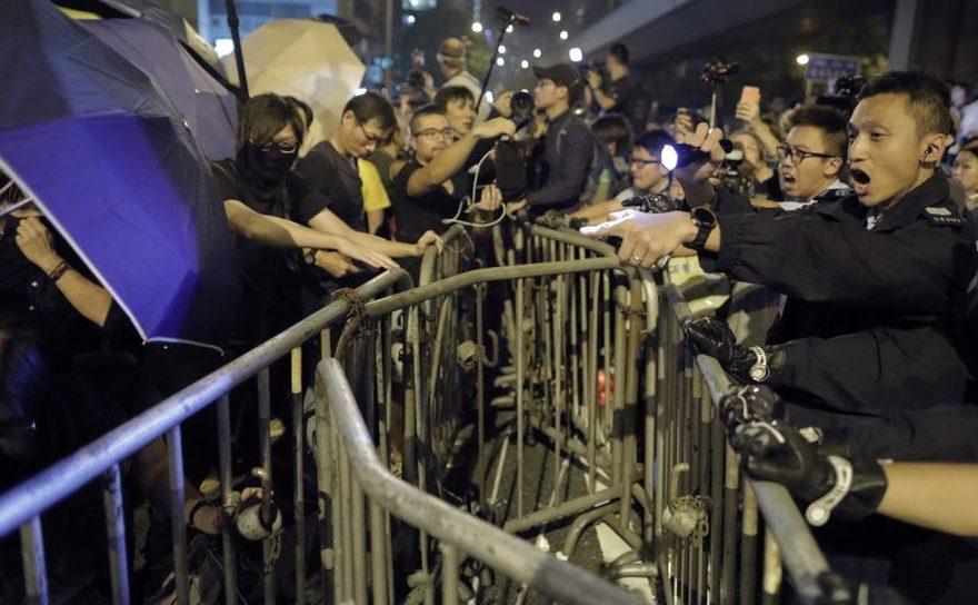 Manifestanţii folosesc umbrele pentru a se apăra de sprayurile cu piper folosite de poliţişti în timpul unui protest în Hong Kong, 6 noiembrie 2016.