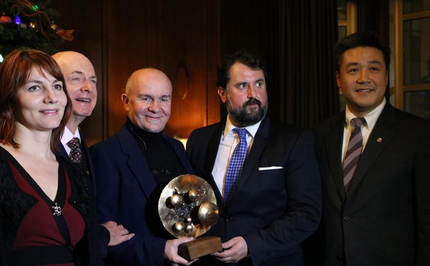 """Raul Dudnic, director executiv al televiziunii ROMEDIA, ţinând în mână scultpura """"NOI"""" oferită ca premiu de d-nul consul Doru Liciu(în mijloc)"""