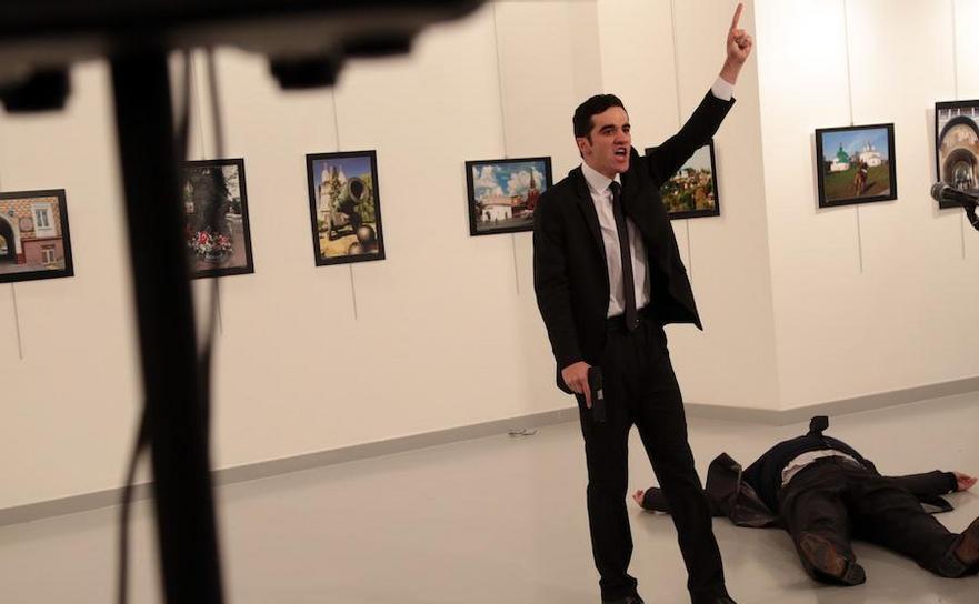 Un bărbat înarmat ameninţă cu o armă după ce l-a împuşcat fatal pe ambasadorul rus în Turcia (dreapta, jos), 19 decembrie 2016, Ankara.