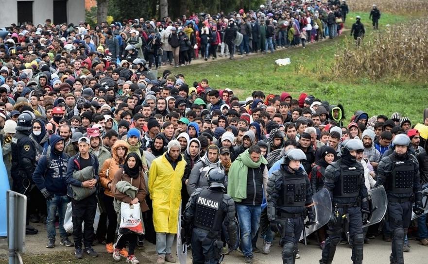Refugiaţii sunt escortaţi de poliţie prin Dobova, Slovenia, în drum spre o tabără de imigranţi, 22 octombrie 2015.