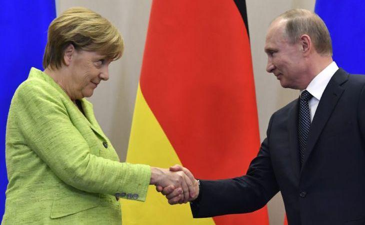 Cancelarul german, Angela Merkel, dă mâna cu preşedintele rus, Vladimir Putin, la finalul unei conferinţe de presă desfăşurată după o întâlnire între cei doi lideri în staţiunea rusească Soci, 2 mai 2017.