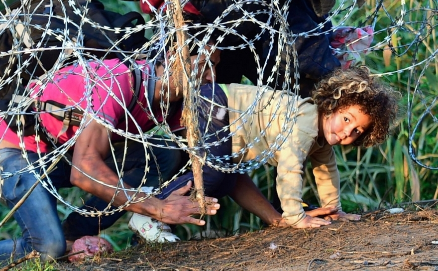 Un grup de refugiaţi trece pe sub un gard de sârmă ghimpată la frontiera ungaro-sârbă, în apropiere de Roszke, Ungaria, 27 august 2015.