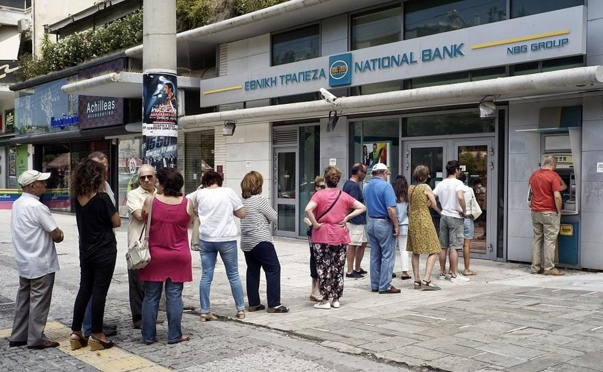 Oamenii stau la coadă pentru a scoate bani de la un bancomat al Băncii Naţionale din Atena, Grecia.