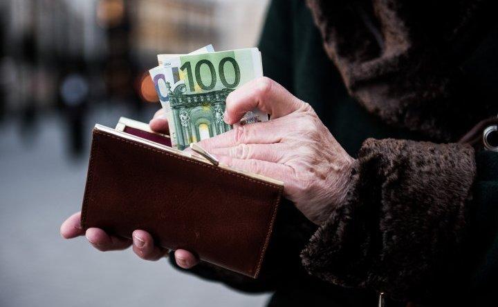 O persoană pune mai multe bancnote euro într-un portmoneu.