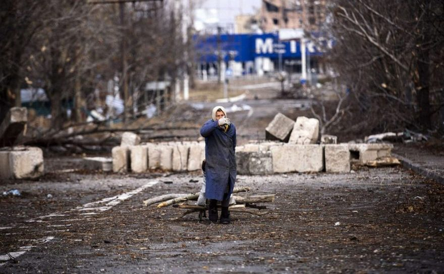 O bătrână trage un cărucior cu lemne pentru foc în apropiere de aeroportul Doneţk din estul Ucrainei