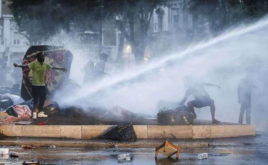 Poliţia italiană foloseşte un tun cu apă pentru a dispersa refugiaţi în centrul Romei, 24 august 2017.