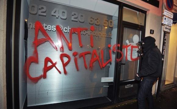 Un membru al  grupului extremist Antifa vandalizează un magazin din Nantes, Franţa, pe  14 februarie 2014
