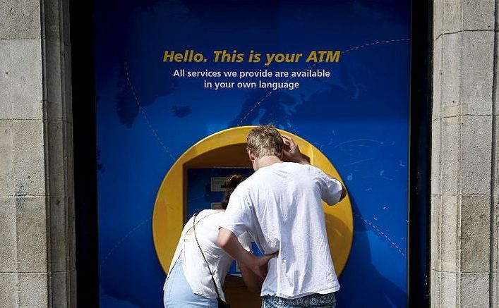 Două persoane folosesc un bancomat Caixa Bank în Barcelona, Spania.