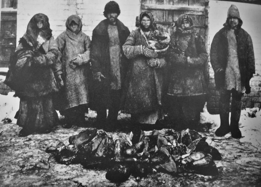 Ţărani fotografiaţi în faţa unor rămăşiţe umane. Canibalismul era răspândit în perioada foametei din Rusia - 1921 şi 1922