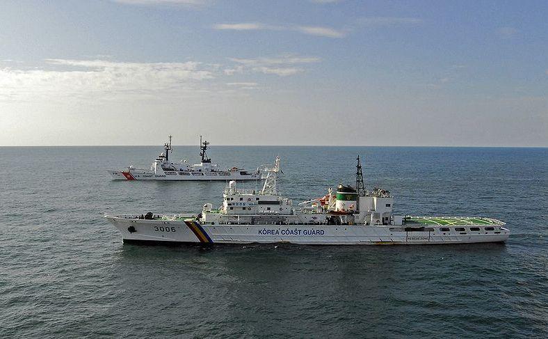 O navă a pazei de coastă sud-coreene alături de o navă pazei de coastă americane (în fundal).