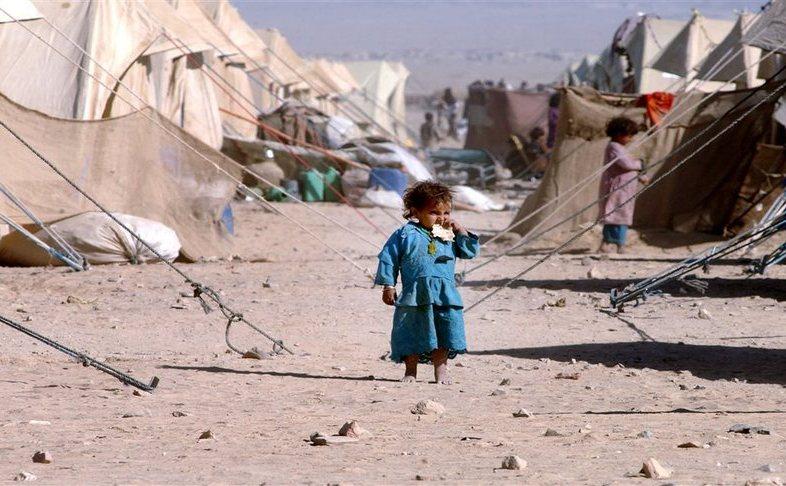 O fetiţă afgană mănâncă o bucată de pâine într-o tabără de refugiaţi din Pakistan, situată la graniţa afgano-pakistaneză.
