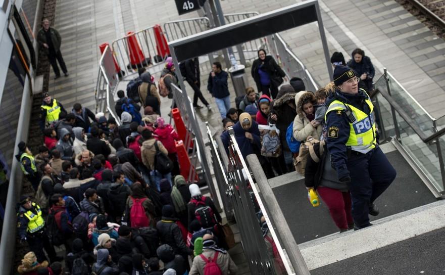 Poliţia conduce refugiaţi de la staţia de tren Hyllie din oraşul Malmo către Agenţia Suedeză pentru Migraţie, 19 noiembrie 2015, Suedia.