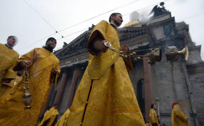 Preoţi ortodocşi ruşi participă la o ceremonie religioasă în faţa Catedralei Sfântul Isaac din St. Petersburg, Rusia.