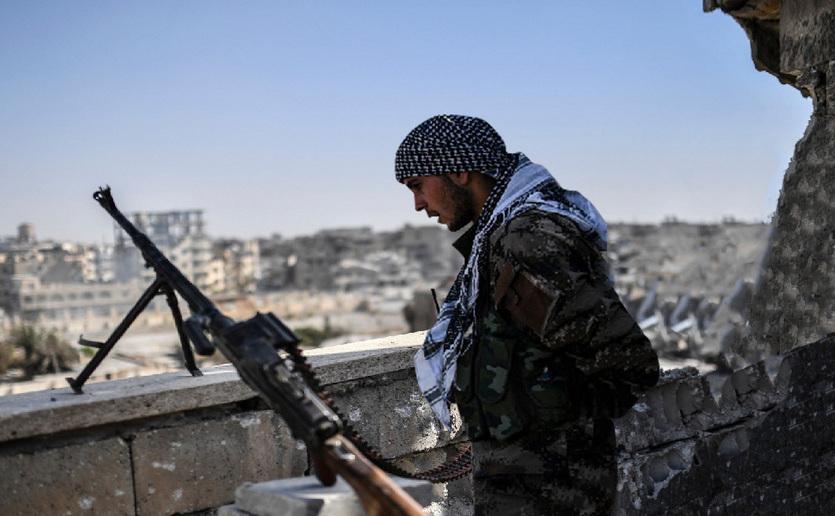 Un luptător al Forţelor Democratice Siriene stă de pază pe acoperişul unei clădiri din Raqqa, Siria, 20 octombrie 2017.