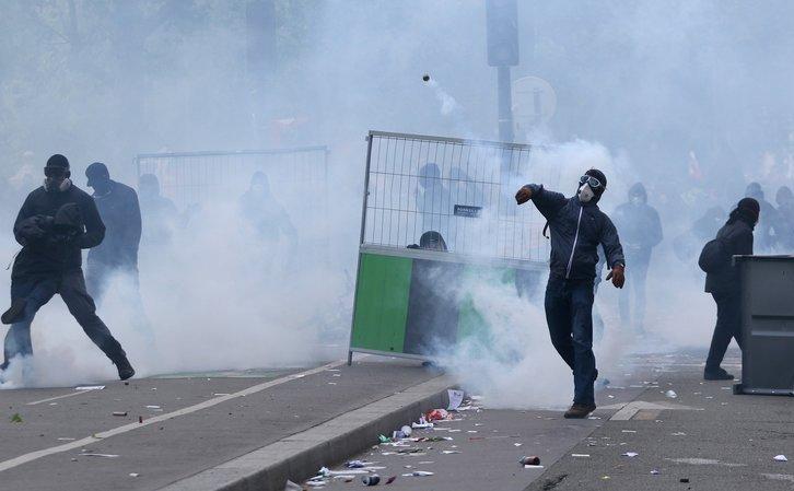 Manifestanţi mascaţi aruncă cu pietre în timpul unor ciocniri cu forţele de ordine în Paris, Franţa, 1 mai 2018.